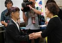 エレベーター事故から12年、港区は6月3日を「港区安全の日」に制定し、遺族と支援者が開いていた集会を共催した。会場に田村弘美さんが訪れると、市川正子さんは手を握って笑顔を見せた=東京都港区で2018年6月3日、佐々木順一撮影