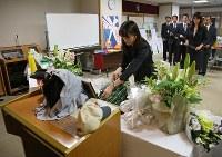 港区は6月3日を「港区安全の日」に制定した。大輔さんのユニホームなど野球道具が展示された献花室では区職員らが花を供えて、手を合わせた=東京都港区で2018年6月3日、佐々木順一撮影