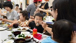 「みなと子ども食堂」で母親(手前)と一緒に食べる男の子。この日のメニューは、ハンバーグ定食で子ども100円、大人300円。育児中の親たちの憩いの場でもある=東京都港区のみなと子ども食堂で2018年9月5日、丸山博撮影
