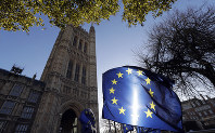 In this Jan. 22, 2019 file photo, the sun shines through European Union flags tied to railings outside parliament in London. (AP Photo/Kirsty Wigglesworth)