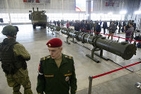 Russian military officers stand by as the 9M729, center, its launcher, left, and the 9M728, right, land-based cruise missiles are displayed in Kubinka outside Moscow, Russia, on Jan. 23, 2019. (AP Photo/Pavel Golovkin)