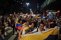 Venezuelan anti-government protesters hold their national flag as they block traffic during a demonstration in Sao Paulo, Brazil, on Jan. 23, 2019. (AP Photo/Victor R. Caivano)
