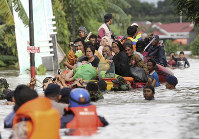Residents ride a makeshift raft as they evacuate their flooded homes in Makassar, South Sulawesi, Indonesia, on Jan. 23, 2019. (AP Photo/Masyudi Syachban Firmansyah)