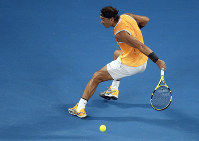 Spain's Rafael Nadal makes a backhand return to Greece's Stefanos Tsitsipas during their semifinal at the Australian Open tennis championships in Melbourne, Australia, on Jan. 24, 2019. (AP Photo/Kin Cheung)