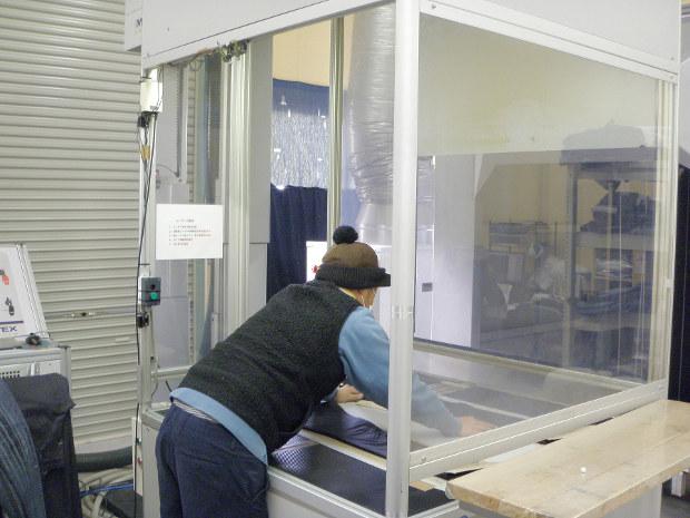 豊和の洗い加工場。レーザー光線加工機にデニム生地を並べる(筆者撮影)