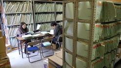 古い診療記録を調べる人たち。MID-NETはこうした情報を、製薬会社を通さずに収集する