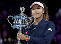 Japan's Naomi Osaka holds her trophy after defeating Petra Kvitova of the Czech Republic during the women's singles final at the Australian Open tennis championships in Melbourne, Australia, Saturday, Jan. 26, 2019. (AP Photo/Aaron Favila)