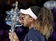 Japan's Naomi Osaka kisses her trophy after defeating Petra Kvitova of the Czech Republic in the women's singles final at the Australian Open tennis championships in Melbourne, Australia, Saturday, Jan. 26, 2019. (AP Photo/Aaron Favila)