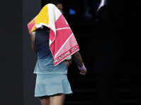 Japan's Naomi Osaka covers her head as she walks from the court after losing the second set to Petra Kvitova of the Czech Republic during the women's singles final at the Australian Open tennis championships in Melbourne, Australia, Saturday, Jan. 26, 2019. (AP Photo/Aaron Favila)