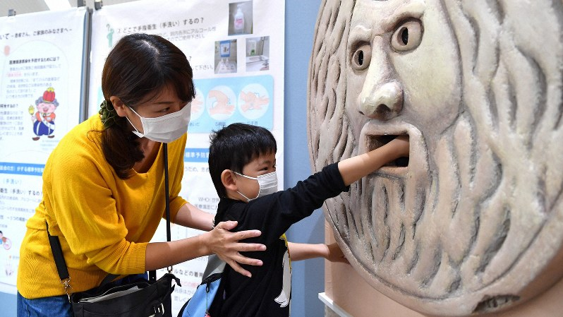 インフルエンザ予防をしようと、消毒液の入った「口」に手を入れる子ども=大阪大病院で