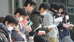 大学入試の直前に、参考書やノートを広げる受験生。受験のストレスもカンジダ発症の一因だ