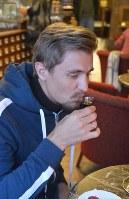 黒バルサムを初めて味わう前に香りをかぐロシア人観光客のアルチョムさんリガで2018年月、大前仁撮影