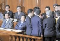 参院本会議で審議が止まり、議長席横に集まった議運委理事の与野党議員らの協議を待つ安倍晋三首相(前列左から2人目)=国会内で2019年1月29日、川田雅浩撮影