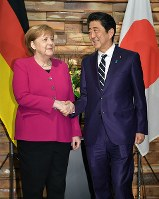 首脳会談を前に握手をするドイツのメルケル首相(左)と安倍晋三首相=首相官邸で2019年2月4日午後6時16分、手塚耕一郎撮影