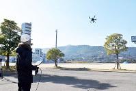 指示を受けながらドローンを飛ばす操縦士=高松市生島町の県消防学校で、山口桂子撮影