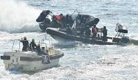G20サミットに向けた合同訓練で、テロリスト役が乗る船舶(左)の進路を塞ぐ海上保安庁のゴムボート=大阪市住之江区で2019年2月5日、山崎一輝撮影