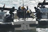 G20サミットに向けた合同訓練で、テロリスト役が乗る船舶(中央)に乗り込む海上保安庁の職員ら=大阪市住之江区で2019年2月5日、山崎一輝撮影