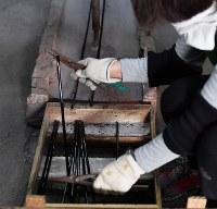 冷えて固まり、カットされるガラス棒=大阪府和泉市の佐竹ガラスで、猪飼健史撮影