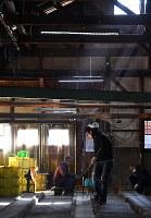 熱したガラスを棒状に伸ばす職人=大阪府和泉市の佐竹ガラスで、猪飼健史撮影