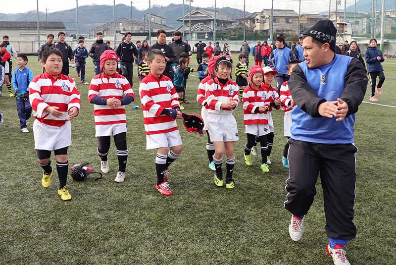御所実ラグビー部の選手をコーチ役に、ダンスを取り入れた体操をする子供たち=奈良県御所市玉手の同校で