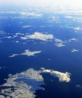 北海道・根室半島の納沙布岬(手前)沖に浮かぶ歯舞群島(中央)=2019年1月30日、本社機「希望」から