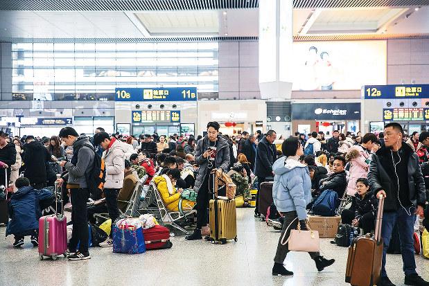 春節の季節には主要都市の空港や駅は旅行客でごった返す(Bloomberg)