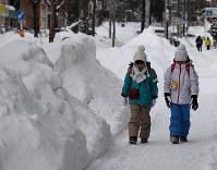 雪が積もる中、寒そうに歩く子供たち=札幌市中央区で2019年2月8日午前7時55分、竹内幹撮影