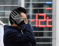 温度計が氷点下12度を示す寒さの中、耳を守るように手をあてる男性=札幌市中央区で2019年2月8日午前8時38分、竹内幹撮影