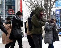 温度計が氷点下12度を示す中、寒そうに歩く人たち=札幌市中央区で2019年2月8日午前8時51分、竹内幹撮影