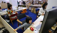 オフィスのパソコンの前に座る米山麦ちゃん(3)。左奥は長女を見守る母親の玲子さん(42)。体験型カタログギフトを企画・販売する会社「ソウ・エクスペリエンス」では保育園に預けることができなかった社員に子連れ出勤を認めている=東京都渋谷区で2019年1月31日午前11時32分、長谷川直亮撮影