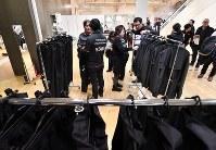 ユニフォームのサイズ確認をする東京五輪都市ボランティア説明会の参加者ら=東京都千代田区で2019年2月9日午前11時46分、宮間俊樹撮影