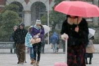 小雪が舞う中を歩く人たち=東京都千代田区で2019年2月9日午後4時29分、玉城達郎撮影
