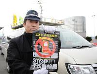ルールを守って無線機を使うよう呼びかけるチラシを持つ大阪府警の警察官=大阪府泉佐野市で、宮川佐知子撮影