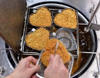 油で揚げられるハート型のチキンラーメン=大阪府池田市で2019年2月6日午後4時1分、山田尚弘撮影