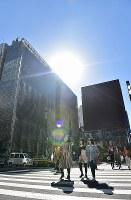 気温が上昇し、コートなどを脱いで歩く人たち=東京都中央区銀座で2019年2月4日午後0時53分、竹内紀臣撮影