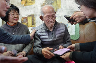 Bae Han-seop receives an atomic bomb survivor's certificate from Keiko Shinozaki, a Nagasaki Municipal Government official, right, in Namhae County, South Korea, on Jan. 28, 2019, as his family and supporters look on. (Mainichi/Takehiro Higuchi)