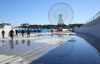 The Kasai Canoe Slalom Centre for the 2020 Tokyo Olympics is seen under construction in Tokyo's Edogawa Ward on Feb. 12, 2019. The Ferris wheel at Kasai Rinkai Park is seen in the background. (Mainichi/Yuki Miyatake)