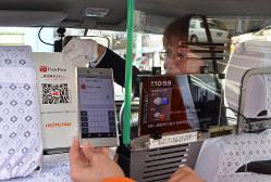 ペイペイのQRコードを示すタクシーの運転手=松山市