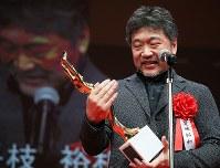第73回毎日映画コンクールの表彰式でトロフィーを見つめる日本映画大賞を受賞した「万引き家族」の是枝裕和監督=川崎市川崎区のカルッツかわさきで2019年2月14日午後5時50分、玉城達郎撮影