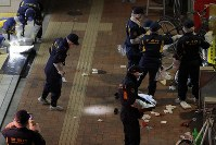 男が刃物で人を切りつけた東京メトロ後楽園駅の出入り口付近を調べる警察官ら=東京都文京区で2019年2月14日午後9時5分、和田大典撮影