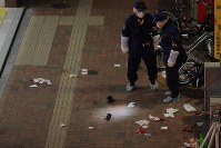 男が刃物で2人を切りつけた東京メトロ後楽園駅の出入り口付近を調べる警察官ら=東京都文京区で2019年2月14日午後8時55分、和田大典撮影