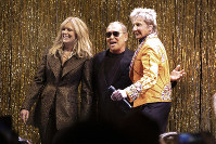 Designer Michael Kors, center, is joined by model Patti Hansen and Barry Manilow on stage after his collection was modeled during Fashion Week in New York, on Feb. 13, 2019. (AP Photo/Richard Drew)