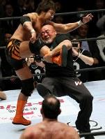 「プロレスリング・マスターズ」でセコンドから試合に乱入し、ドラゴンスクリューを決める武藤敬司(右)=東京都文京区の後楽園ホールで2019年2月15日、山本晋撮影