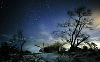 被災した家屋などが残る吉野地区の夜景。写真右側の光跡は航空機(30秒間露光)=北海道厚真町で2019年1月29日18時25分、貝塚太一撮影