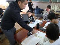 児童の発言がリアルタイムで「可視化」されるタブレット端末を手に各班を回って声をかける大谷哲弘教諭(左)。机の中央にあるのが多機能スピーカー=京都市下京区で、飼手勇介撮影