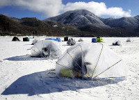People fish for Japanese smelt in small, snail-shaped tents on the frozen surface of Akagi Onuma Lake in the Gunma Prefecture city of Maebashi, north of Tokyo, on Feb. 12, 2019. (Mainichi/Masahiro Ogawa)