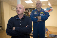 In this March 26, 2015 file photo, U.S. astronaut Scott Kelly, right, crew member of the mission to the International Space Station, stands behind glass in a quarantine room, behind his brother, Mark Kelly, also an astronaut, after a news conference in the Russian-leased Baikonur, Kazakhstan cosmodrome. (AP Photo/Dmitry Lovetsky)