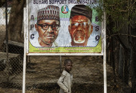 A young boy scavenges for re-sellable items from garbage on the streets, as he walks past a sign showing incumbent President Muhammadu Buhari, left, and local party official Mustapha Dankadai, right, in Kano, northern Nigeria on Feb. 15, 2019. (AP Photo/Ben Curtis)