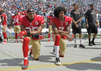 In this Sept. 18, 2016, file photo, San Francisco 49ers' Colin Kaepernick (7) and Eric Reid (35) kneel during the national anthem before an NFL football game against the Carolina Panthers, in Charlotte, N.C. (AP Photo/Mike McCarn)