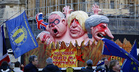 Anti-Brexit demonstrators stand next to a van with large cartoon style portraits of leading British politicians including, from right, Prime Minister Theresa May, Boris Johnson, Michael Gove, David Davis, outside the Palace of Westminster in London, Thursday, Feb. 14, 2019. British lawmakers are holding another series of votes on Brexit legislation Thursday. (AP Photo/Alastair Grant)